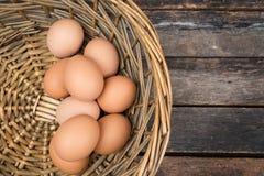 Huevos en cesta en fondo de madera Imagen de archivo libre de regalías