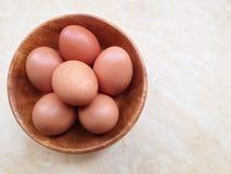 Huevos en cuenco de madera en de madera imagenes de archivo