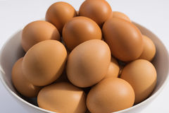 Huevos en cuenco en un fondo del blanco de la tabla Imágenes de archivo libres de regalías