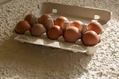 Huevos en el blanco del paquete en la tabla Imagenes de archivo