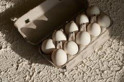 Huevos en el blanco del paquete en la tabla Imagen de archivo libre de regalías