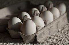 Huevos en el blanco del paquete en la tabla Foto de archivo libre de regalías