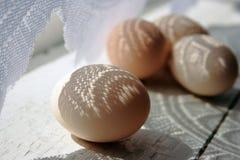 Huevos en el windowsill en la cortina del curtai Foto de archivo