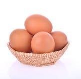 Huevos en la cesta aislada en el fondo blanco Foto de archivo