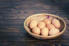 Huevos en la cesta de bambú en la tabla de madera Fotografía de archivo libre de regalías
