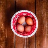Huevos en la cesta en la textura de madera Fotos de archivo