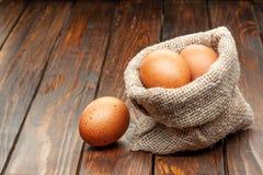 Huevos en saco de la arpillera en un viejo fondo de madera imagenes de archivo