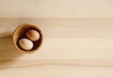 Huevos en un cuenco de madera Fotografía de archivo