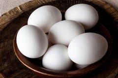 Huevos en un cuenco en el primer de la tabla de cortar desde arriba Fotos de archivo
