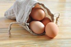Huevos en un saco encima de la madera rústica Fotos de archivo