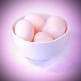 Huevos en un tazón de fuente con las plumas Imágenes de archivo libres de regalías