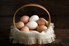 Huevos en una cesta de la abedul-corteza y un paño de lino fotos de archivo