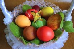Huevos en una cesta de mimbre con una mariposa Imagen de archivo