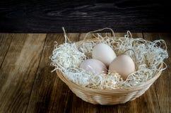 Huevos en una cesta de mimbre rústica en la tabla de madera Fotos de archivo
