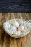 Huevos en una cesta de mimbre rústica en la tabla de madera Fotografía de archivo libre de regalías