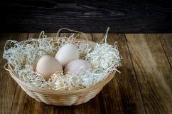 Huevos en una cesta de mimbre rústica en la tabla de madera Imágenes de archivo libres de regalías
