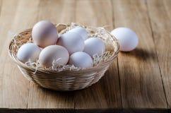 Huevos en una cesta de mimbre rústica en la tabla de madera Foto de archivo libre de regalías