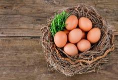 Huevos en una cesta en un fondo de madera Imagen de archivo