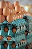Huevos frescos apilados en los cartones en el mercado Imágenes de archivo libres de regalías