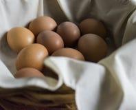 Huevos frescos de la granja en una cesta alineada lino suave Fotos de archivo