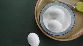 Huevos frescos del pollo en cuenco de cer?mica con colores en colores pastel en fondo verde almacen de video