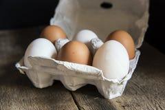 Huevos frescos en cartón de huevos en el st retro del vintage natural cambiante de la iluminación Fotos de archivo libres de regalías