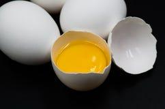 Huevos frescos en el fondo negro Imagen de archivo