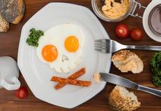 Huevos fritos bajo la forma de cráneo en la tabla de madera Fotografía de archivo libre de regalías