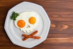 Huevos fritos bajo la forma de cráneo en la tabla de madera Fotos de archivo libres de regalías