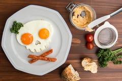 Huevos fritos bajo la forma de cráneo en la tabla de madera Foto de archivo libre de regalías