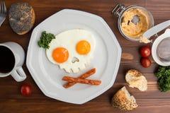 Huevos fritos bajo la forma de cráneo en la tabla de madera Foto de archivo
