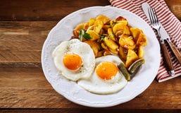 Huevos fritos con las patatas y el pepinillo curruscantes de la carne asada Imágenes de archivo libres de regalías