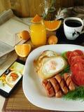 Huevos fritos con las salchichas en una placa blanca y un smartphone con una foto de la comida en la pantalla foto de archivo libre de regalías