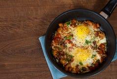 Huevos fritos con las verduras, las setas y el queso en un sartén Fotos de archivo
