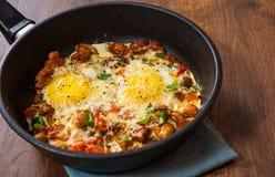 Huevos fritos con las verduras, las setas y el queso en un sartén Imágenes de archivo libres de regalías