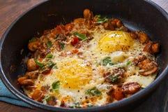 Huevos fritos con las verduras, las setas y el queso en un sartén Foto de archivo