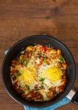 Huevos fritos con las verduras, las setas y el queso en un sartén Imagen de archivo