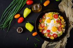 Huevos fritos con las verduras - shakshuka en un sartén en un fondo negro Imagenes de archivo