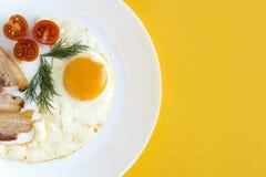 Huevos fritos con los tomates, el tocino y el eneldo Imágenes de archivo libres de regalías
