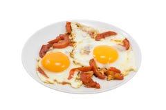 Huevos fritos con los tomates en blanco Imagen de archivo libre de regalías