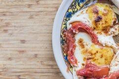 Huevos fritos con los tomates en la placa del color Imagen de archivo libre de regalías