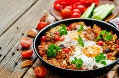 Huevos fritos con pimientas, los tomates, la quinoa y las setas Imagen de archivo