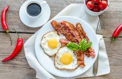 Huevos fritos con tocino en la tabla de madera Foto de archivo libre de regalías