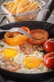 Huevos fritos con tocino y tomates en una cacerola vieja del arrabio foto de archivo libre de regalías