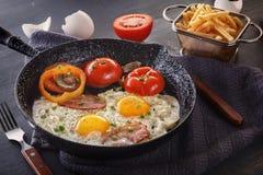 Huevos fritos con tocino y tomates en una cacerola vieja del arrabio con las patatas fritas en una tabla gris foto de archivo