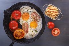 Huevos fritos con tocino y tomates en una cacerola vieja del arrabio con las patatas fritas en una tabla gris fotos de archivo libres de regalías