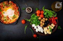 Huevos fritos del desayuno con las verduras - shakshuka en un sartén en un fondo negro en el estilo turco Foto de archivo libre de regalías