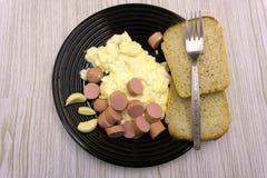 Huevos fritos del desayuno rústico modesto, aceitunas de los pepinos de los tomates y salsa de tomate fotos de archivo libres de regalías