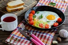 Huevos fritos en cacerola con el tomate, el pan, la pimienta y el perejil imagenes de archivo