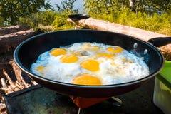 Huevos fritos en el fuego en un alza fuera de la ciudad Imagenes de archivo
